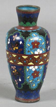 "JAPANESE CLOISONNE VASE Japanese cloisonne vase with center brown gold flecked band, light and dark blue panels with polychrome floral decoration. No mark. Size: 5 1/8""H, 1 1/4""Diam. top, 2 1/2""Diam. widest part, 1 1/4""Diam. base. Condition: several small flakes or chips on surface, other age appropriate wear."