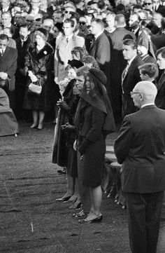 11/25/63: Jacqueline and Robert Kennedy listen to the final tributes to JFK.