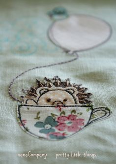 One adorable little hedgehog, in a tea cup, embroidered onto a towel.(: TOO much cute...