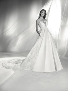 RIA: Majestic wedding dress with a voluminous skirt that contrasts with the form-fitting tattoo bodice. A special and different design. Pronovias 2018 Collection