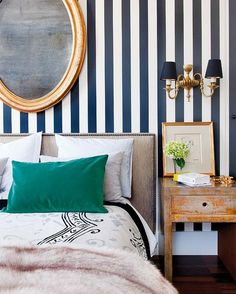 Eclectic bedroom navy blue and white vertically stripes walls and gold-leaf double wall sconce with navy shades