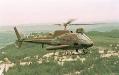 A AS 550 helicopter in flight fitted with iat 20mm gun type M621 and the FN Hershal twin 7.62mm
