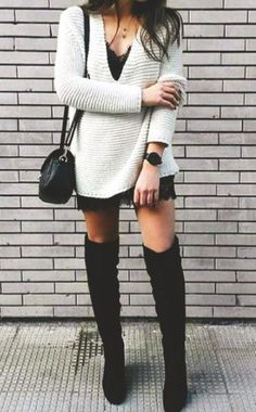 a white deep V neck sweater over a black lace dress, tall black suede boots and a black crossbody