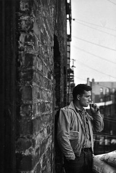 Remembering Jack Kerouac (3/12/22 - 10/21/69) Great shot of The Beat Poet smoking a cigarette at his apartment on his fire escape in the Lower East Side, New York City. Photo by Allen Ginsberg, 1953