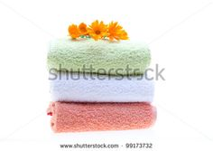Pile of towels with calendula flowers on top, isolated on white background.
