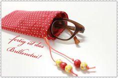 Heute habe ich für Euch ein schnelles Projekt zum Nachnähen. Das Brillenetui: Materialien: 2 verschiedenfarbige Stücke Stoff (á 22cm x 22cm), eine Schnur, 3 Perlen, Schere, Stift, Stecknadeln Nachd…