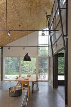 Saw tooth building, glass garage door, suspended lighting tracks, plywood ceiling, polished concrete floor, clerestory