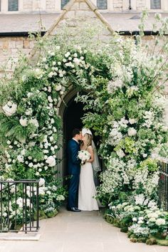 Bride & Groom Flower Arch Portrait - M&J Photography | Elegant London Wedding | White & Greenery Florals