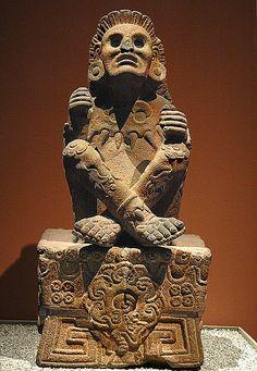 """Xochipilli est un dieu aztèque associé à l'amour, à la beauté, aux fleurs, au printemps, à la jeunesse, aux jeux, aux arts, à la poésie, à la musique & à la danse. Son nom contient les mots nahuatl xochitl (fleur) et pilli (prince, noble ou enfant), il signifie donc le """"prince des fleurs"""". Cette divinité est également associée à l'homosexualité - Cette statue provenant de Tlalmanalco le représente les jambes croisées, assis sur son trône - Musée national d'anthropologie, Mexico."""
