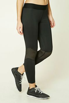 A pair of stretch-knit athletic leggings featuring an elasticized band on waist, contrast and netted-mesh panels, seam-stitched accents, and moisture management.