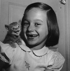 A little girl with a cat on her shoulder . . . little girls and kittens, always a great combination