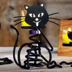 "Stones.  Skeletal kitty can't resist a fish. Black matte-finished metal with glass votive cup. For use with a votive or tealight, sold separately. 7 1/2""h."