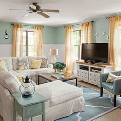 This comfy gathering spot features a large sectional sofa and handcrafted media set, surrounded by cheery blue-green walls and crispy white wainscoting.