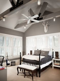 source: Dillon Kyle Architecture  Open, vaulted ceiling with pendant lighting. Gray walls painted Storm by Benjamin Moore. White plantation shutters, glossy black bed with charcoal striped bedding and cream throw blacket. White stag mount, white nightstand and metallic table lamps.