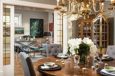 Dining room, tufted chairs, gold chandelier, pocket doors, hardwood floor