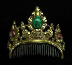 """An ornamental crown/comb. Tibet/Nepal, 18th c or earlier. The basic metal used is copper, which is covered with a thin layer of solid gold (not gilding). The central stone is a turquoise and the other two are corals of great age. The face in the middle is a Kirthimuka (""""Face of Glory"""").  (Joost Daalder)"""