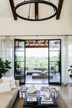 Indoor/outdoor living space with a large chandelier and steel doors