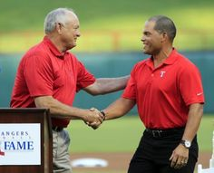 "Former Texas Rangers catcher Ivan ""Pudge"" Rodriguez shares a handshake with team CEO Nolan Ryan, left, during Rodriguez's induction into the Texas Rangers Hall of Fame"
