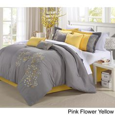 The light grey comforter features delicate floral embroidery in aqua. Shams and decorative pillows add a vibrant touch to this fabulous woven polyester bedding set.