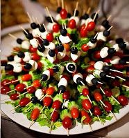 Tomatoes, olives, mozzarella and cucumber skewers inserted into a half a head of lettuce.