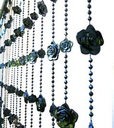 "Gothic Black roses with excellent detail adorn this beaded curtain. There are two sizes of roses on each strand: 1 1/4"" inches and 3/4"" inch in diameter. There are 23 strands of beads on a 36"" wide pi"