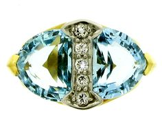 Aquamarine and diamond ring by Tiffany & Co, circa 1950. Stunning kite shaped aquamarines one to either side of a diamond border, with a total approximate combined weight of 4.00ct. Fitted diamond divider is grain set with five round brilliant cut diamonds, having an approximate total weight of 0.20ct. Mounted and set in platinum and yellow gold with a carved shank.