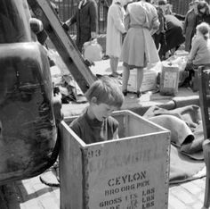 Titled 'A place to read', this photo shows a boy sitting in a tea chest in the busy Cumberland Street market which is still held every Saturday in Dublin. From the National Photographic Archive