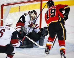 Arizona Coyotes' goalie Mike Smith, left, catches a shot in his pads from Calgary Flames' Matthew Tkachuk during the first period of an NHL preseason hockey game in Calgary, Alberta, Wednesday, Oct. 5, 2016. (Jeff McIntosh/The Canadian Press via AP)
