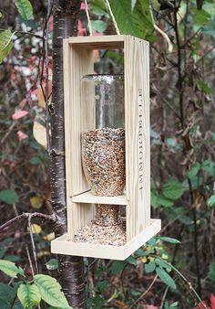 Mangeoire pour oiseau avec une caisse à vin et une bouteille en verre