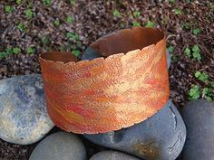 Autumn Flame Cuff Instructor: Kat Clark Workshop Fee:  $35 Sunday, October 30 (1-4pm) Autumn Flame cuff is a wonderful expression of metal and color. Fun exploration ensues using Gilder's Paste to create an amazing faux finish on metal. Students will learn to create a cuff blank with a serrated edge. Texturing created an interesting surface for the color. Previous sheet metal working experience is required. Materials list.