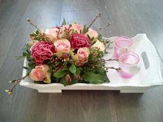 Bloemstuk met rozen en anjers op dienblad.
