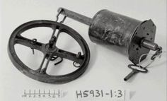 "H5931 Spit, clockwork, 'Bottle Jack', roasting spit, with key and cast iron balance wheel, England, 19th century (OF) English clockwork 'Roasting Jack' (Late 19th century) 4 3/4"" x 31/2"" barrel, 7 1/2"" spit wheel, slotted & carrying movable rings. Marked - Powerhouse Museum Collection"