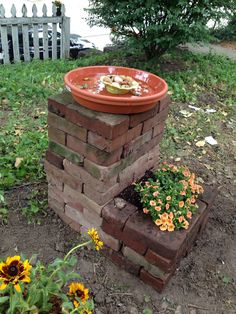 We built a bird bath and added a flower box by repurposing some old bricks food in the back yard. The terra cotta bath is a water dish and was purchased at the garden store.