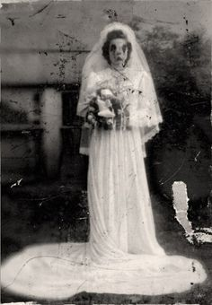 Post-mortem photo of a young woman in her bridal gown? This is just a strange picture period. The picture is pretty distorted and damaged, so its hard to say...