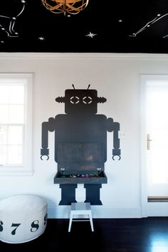 Combining a giant wall decal and reclaimed wood, the designers created a storage unit and play desk that looks like a giant Lego robot.