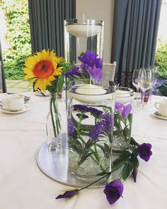 Trio vase centrepiece with floating candles, purple flowers and sunflowers #piecesandposies