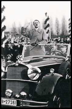 There are tens of thousands of photos of Hitler standing upright in his car, saluting the crowds. This is one of the better ones. Kempka drives. (via putschgirl)