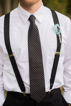 Groomsmen wearing black pants, suspenders and polka-dot skinny tie and a feather boutonniere