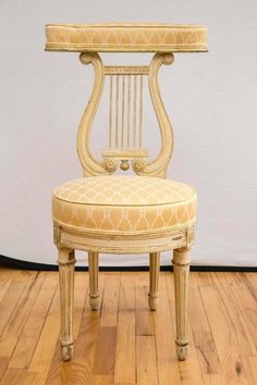 "Early 19th c.; A cream painted wood, yellow upholstered voyeuse. A chair on which a ""voyeur"" would kneel or sit astride while watching a group engage in a game of cards but not actually being a player in the game. The chair would be positioned with its back towards the players and be off to the side of the game table."