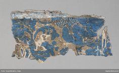 Tapetprovet består av 15 st. fragment. Grundfärgen är beige, med schablonmönster i blått.