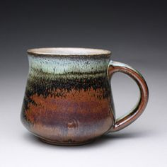 This handmade ceramic mug is glazed with an orange shino and wood ash glaze. The color changes were caused by the varying atmosphere and flames