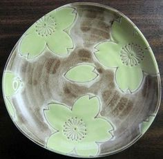 Fantastic stylized shiny lime green textured flower on tan matte glaze plate. Very striking. Curved lip on shallow footed base. Quality--Made in Japan. Perfect for wall, cabinet, or snack.