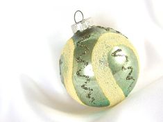 This unique West Germany Shiny Brite Christmas ornament is truly different! With a faded greenish/ bluish background, the white/yellow mica