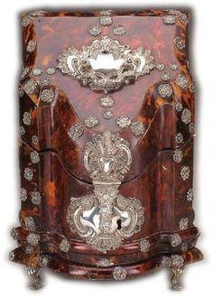 Rara barretina D. José, em madeira revestida a tartaruga e aplicações várias de prata (escudete, fecho, dobradiças, pés e florões)