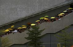 """HONGKONG-CHINA/OCCUPYcPro-democracy protesters carrying yellow umbrellas, symbol of the Occupy Central civil disobedience movement, gather on the stairs outside government headquarters in Hong Kong, China September 28, 2015. Monday marks the first anniversary of the Occupy Central or """"umbrella"""" movement, demanding universal suffrage in the territory. REUTERS/Bobby Yip"""