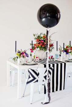 Consider a black and white theme for your wedding reception and just soften up the look with lots of bright flowers.