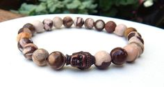 Unique jasper mens buddha bracelet is made with an Antique Red Copper Buddha bead surrounded by 8mm Zebra Jasper. Awesome stones with a random patterns of colors. Zebra Jasper Properties: This is a nu