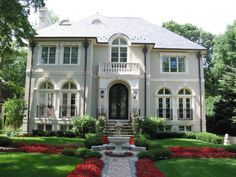 Gorgeous French inspired home exterior with Juliet balconies and fountain by Reynolds Architecture.