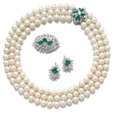 CULTURED  PEARL,  EMERALD  AND  DIAMOND  PARURE	  	  Comprising:  a  necklace  composed  of  three  strands  of  cultured  pearls   to  a  clasp  set  with  brilliant-cut  and  marquise-shaped  diamonds  and  pear-shaped  emeralds;  together  with  a  brooch  and  a  pair  of  earrings  set  with  emeralds  and  diamonds. (Sothebys)