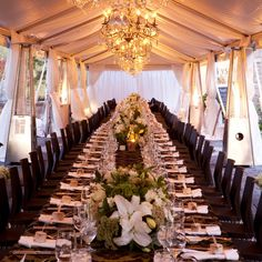Intimate wedding reception with one long table, black wooden chairs, hanging crystal chandeliers and low floral arrangements | Sandra Tenuto Photography | Verbena Floral Design, Victoria, BC